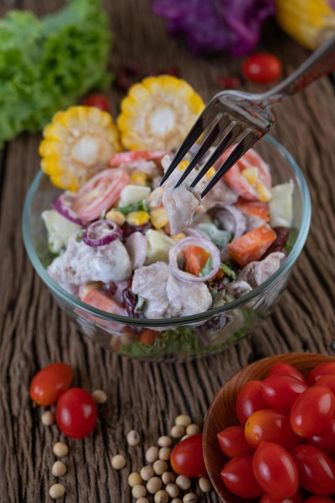 Obst- und Gemüsesalat in einer Glasschüssel auf Holztisch foto