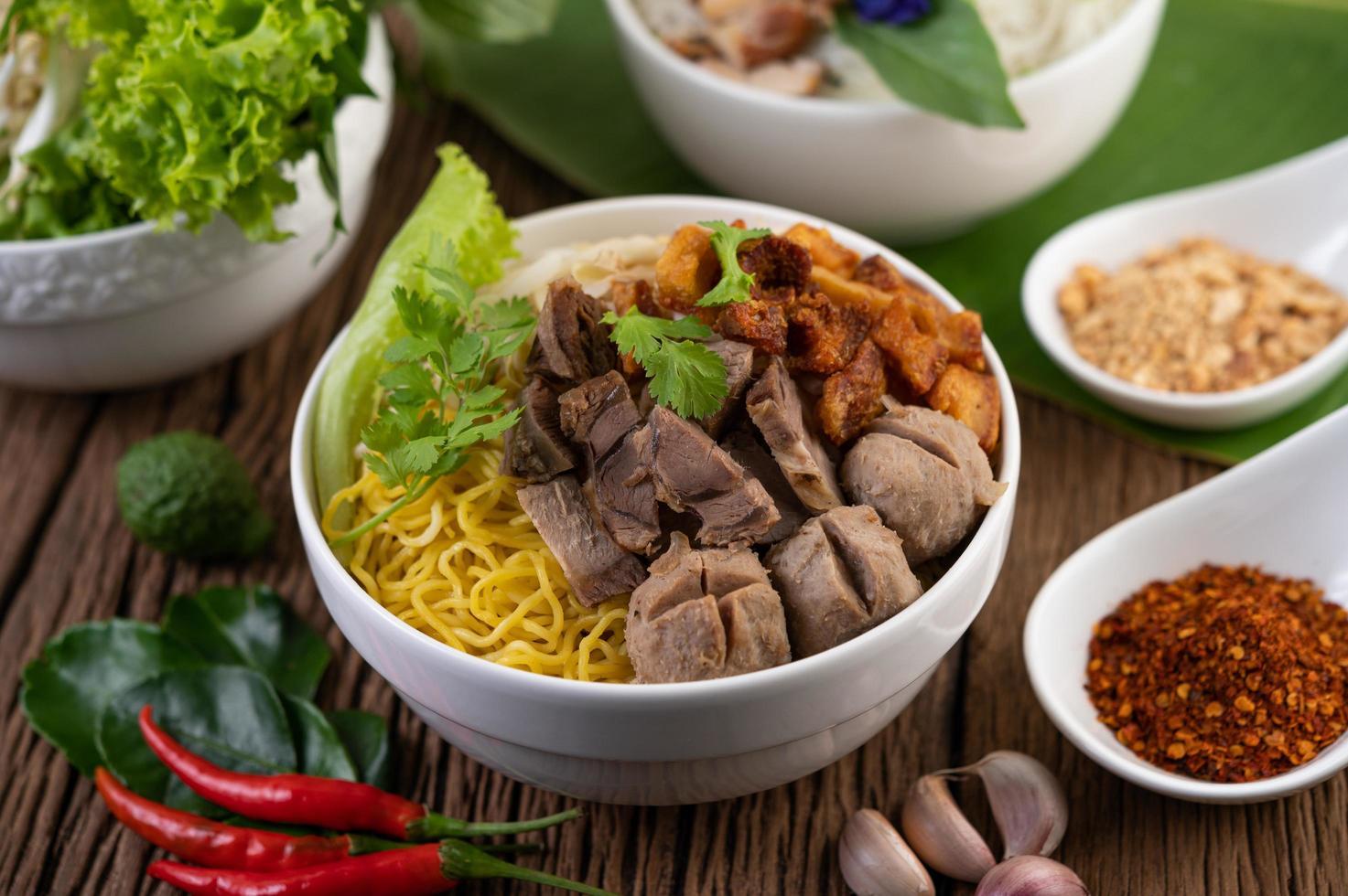 gelbe Nudeln mit knusprigem Schweinefleisch und Fleischbällchen foto
