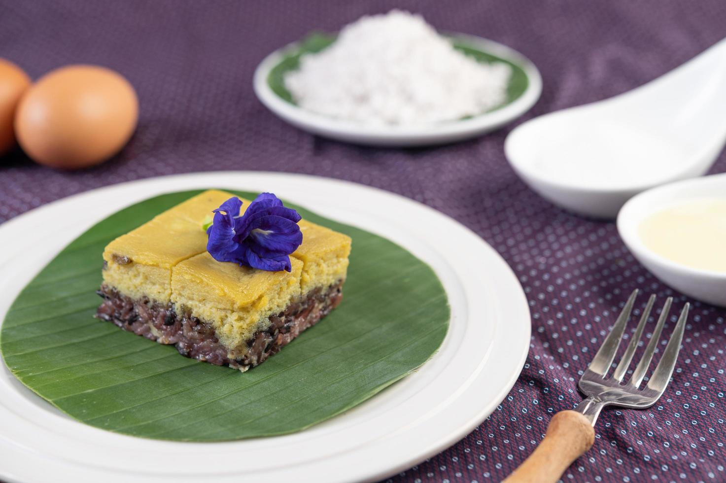 schwarzer klebriger Reis auf einem Bananenblatt in einem weißen Teller mit Schmetterlingserbsenblüten foto