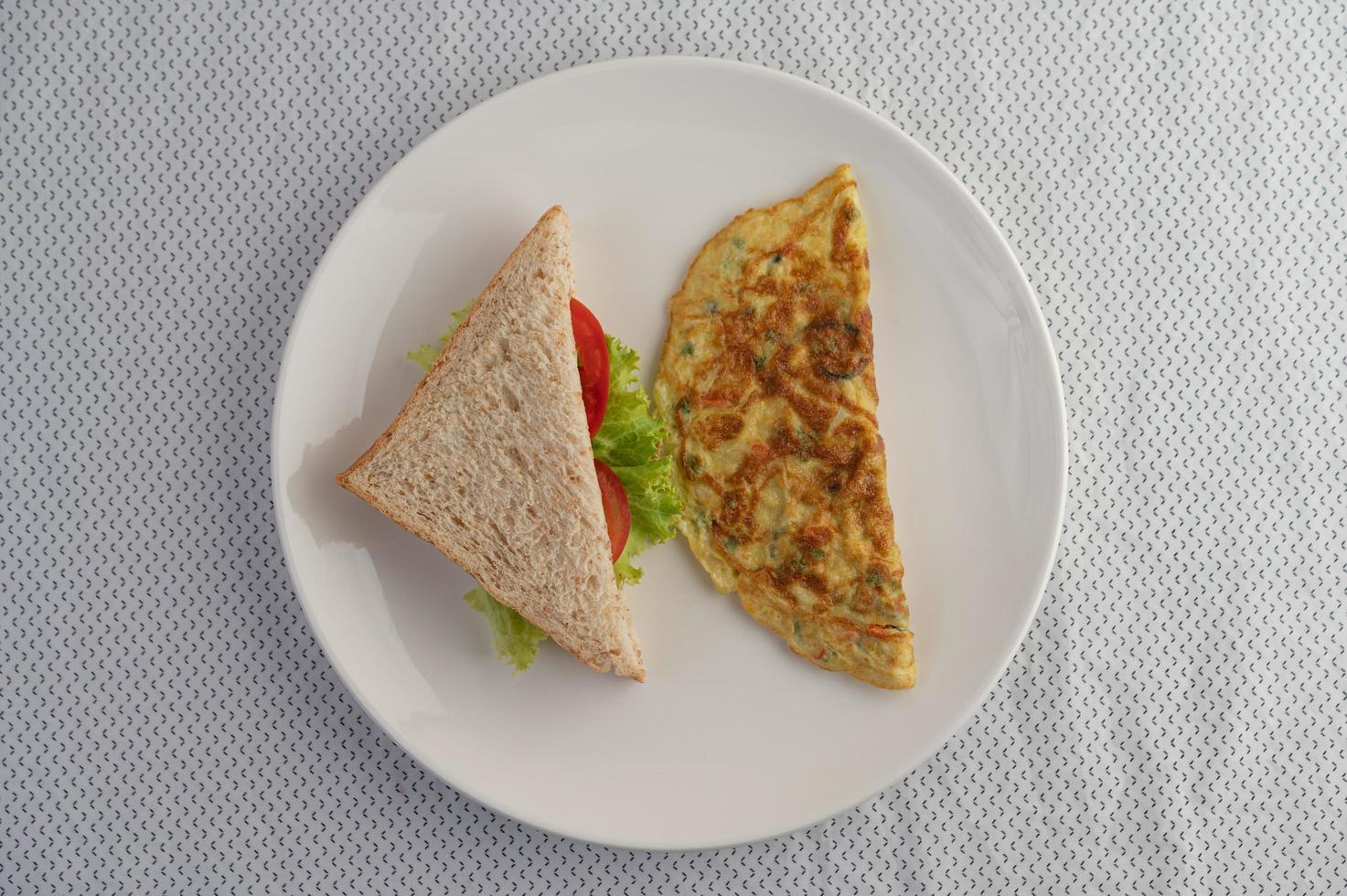 ein Ei Omelett und Sandwich auf einem weißen Teller foto