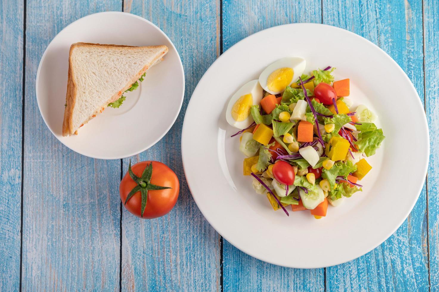frischer Salat auf einem weißen Teller mit Sandwich und Tomaten foto