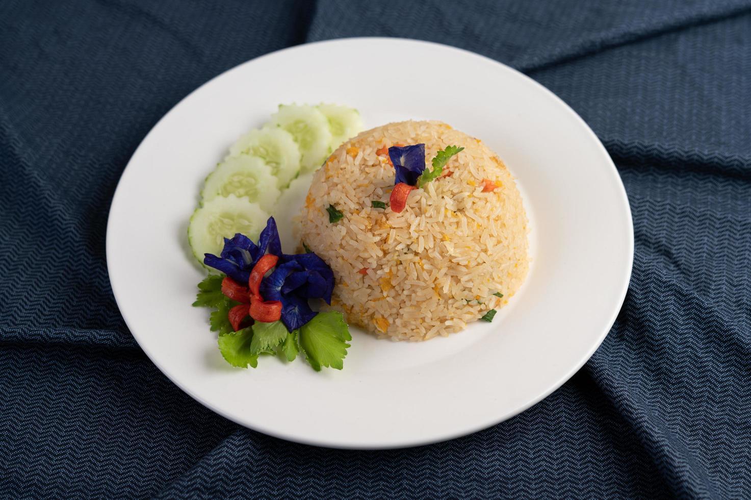 Ei gebratener Reis auf einem weißen Teller mit zerknittertem Stoff foto