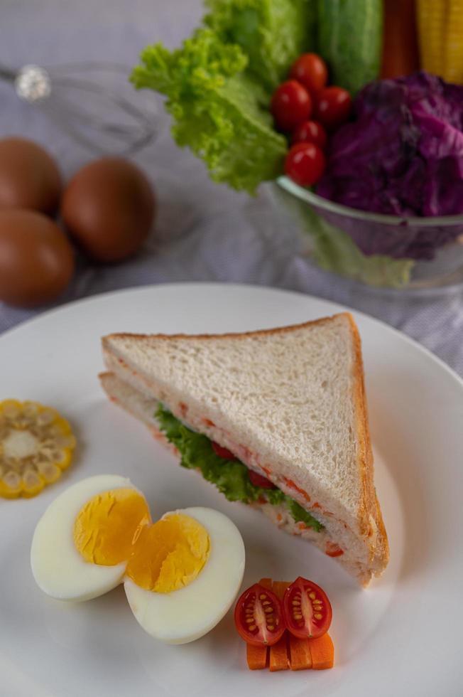 gekochte Eier, Mais, Tomatensandwich auf einem weißen Teller foto