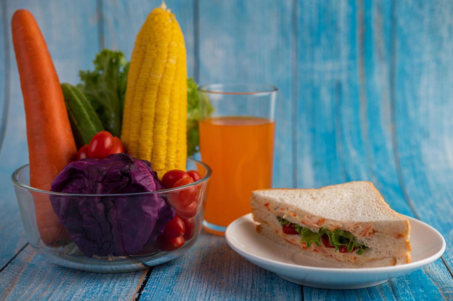 Orangensaft, Sandwich und Gemüse foto