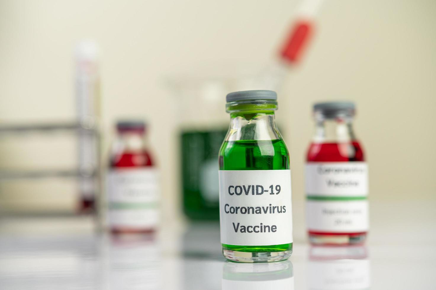 der Impfstoff gegen Covid-19 in roten und grünen Flaschen foto
