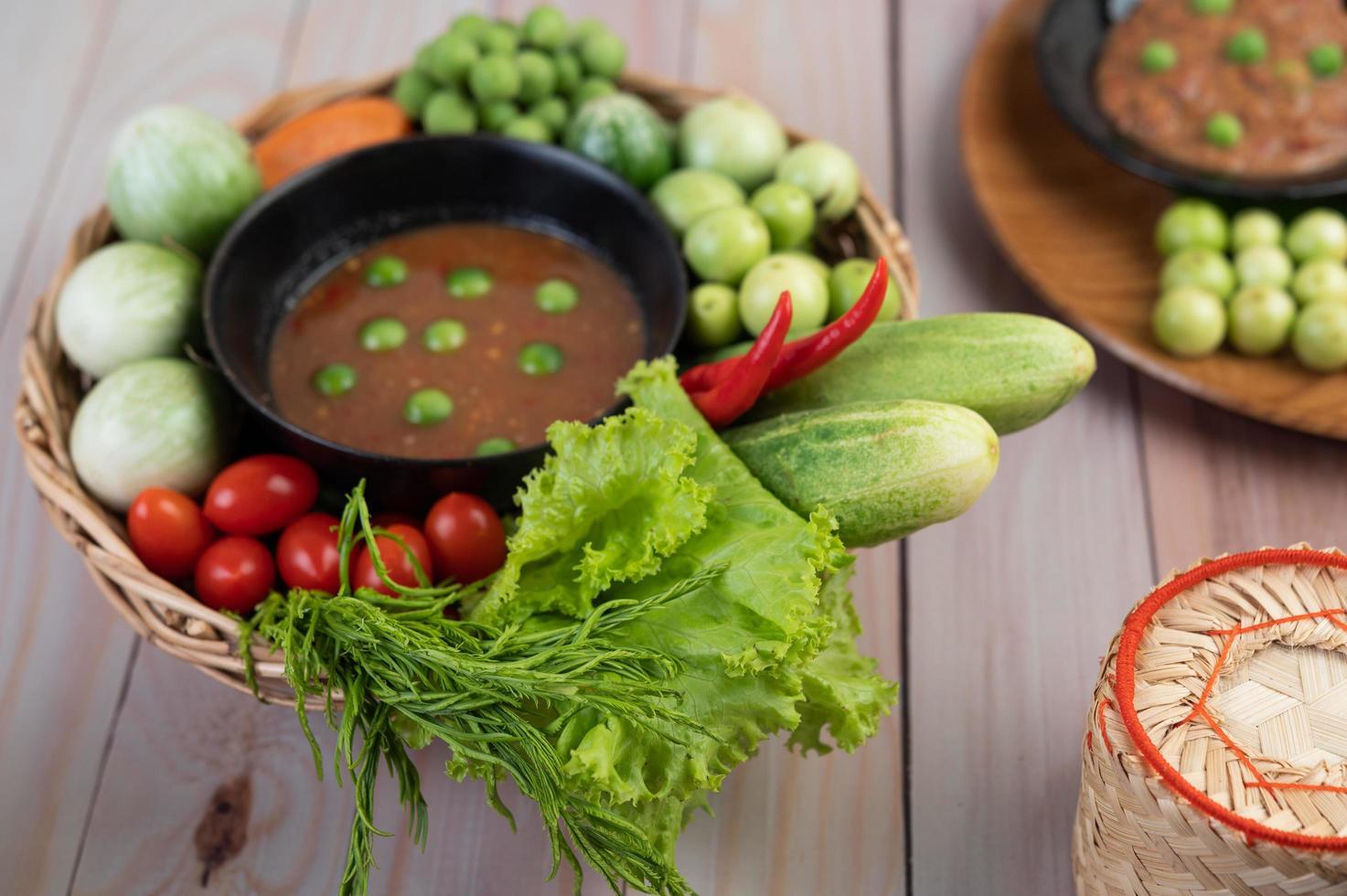 Chilipastenpaste in einer Schüssel mit Auberginen, Karotten, Chili und Gurken in einem Korb foto