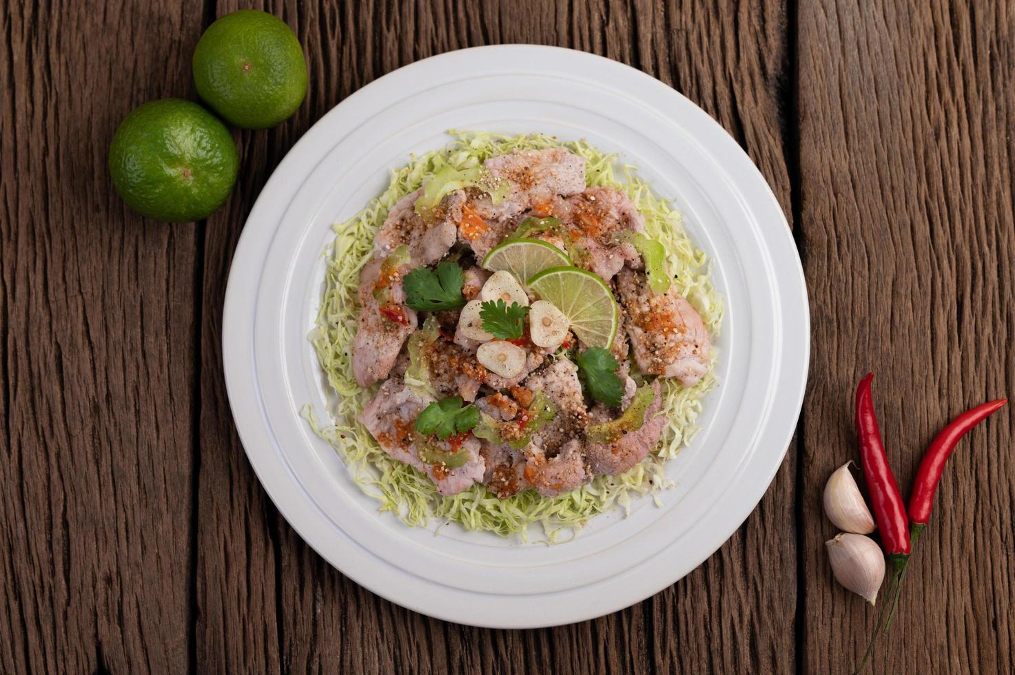 würziger Limettenschweinefleischsalat mit Galangal, Chili und Tomaten foto