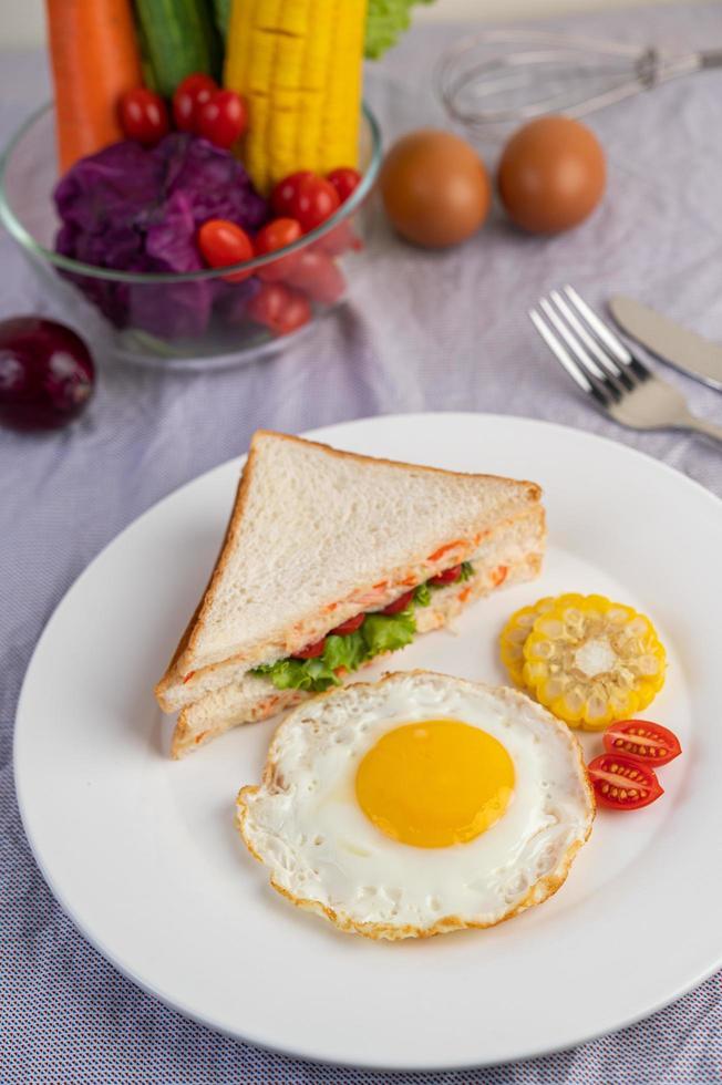 Spiegelei-Frühstück mit Ei, Salat, Kürbis, Gurke, Karotte und Mais foto