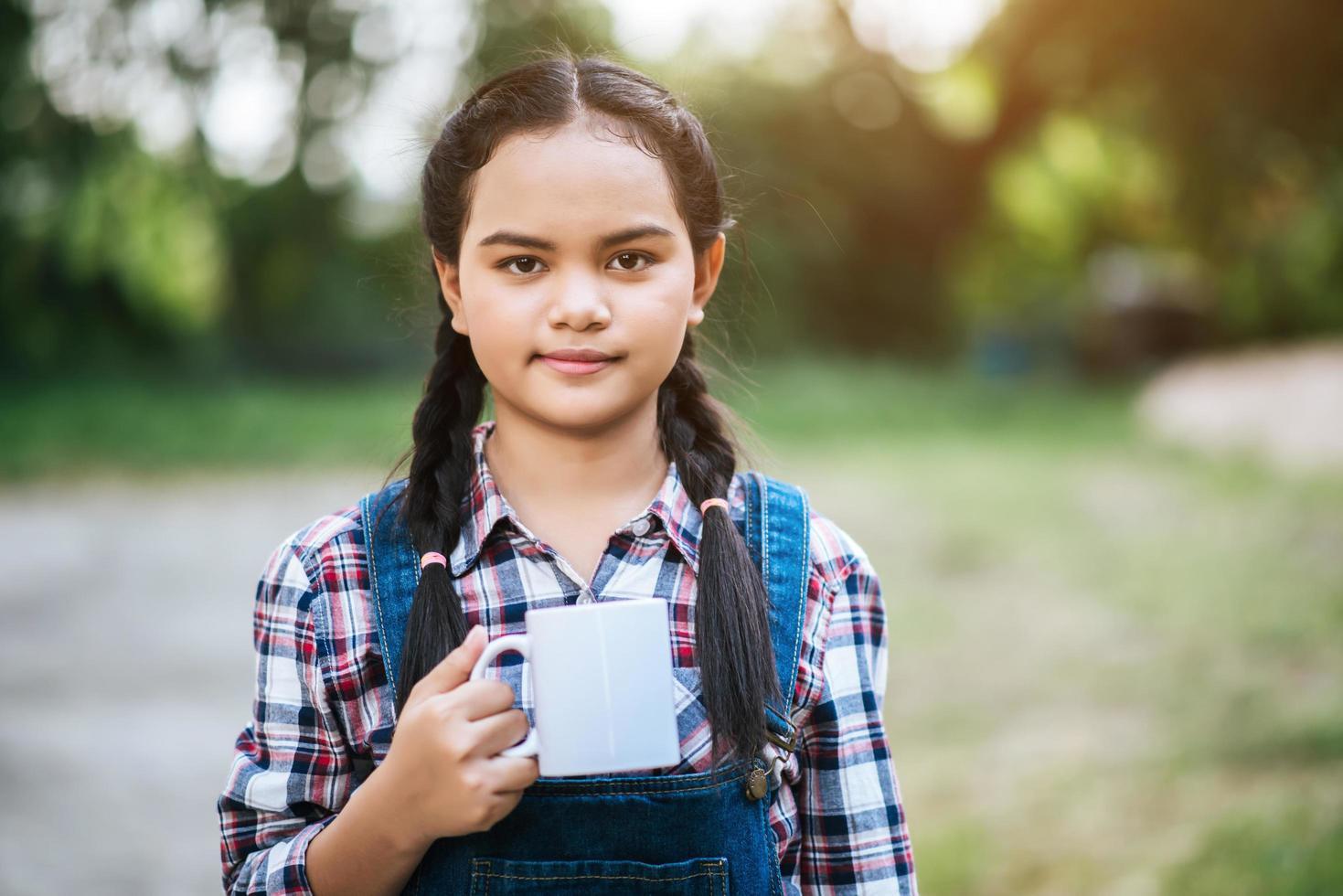 junges Mädchen, das einen Keramikbecher hält foto