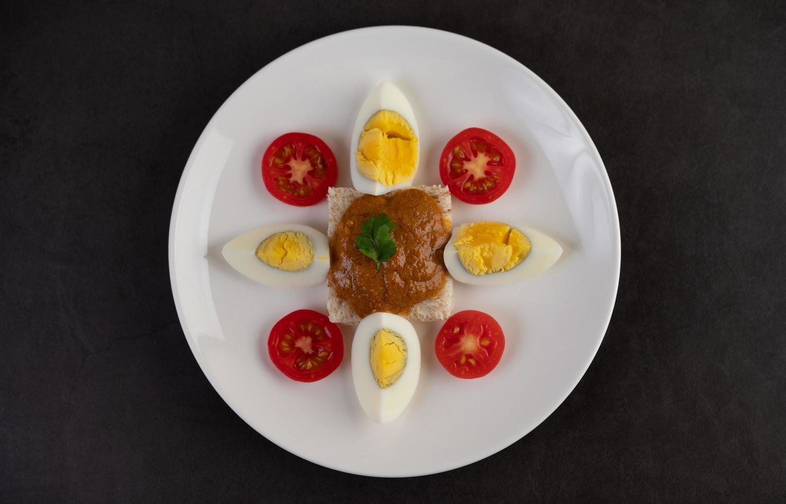 Brot mit Chilipaste mit gekochten Eiern und Tomaten belegt foto