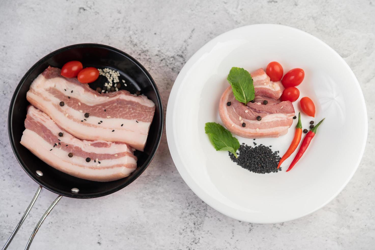 Schweinebauch in einer Pfanne mit Pfeffersamen, Tomaten und Gewürzen foto
