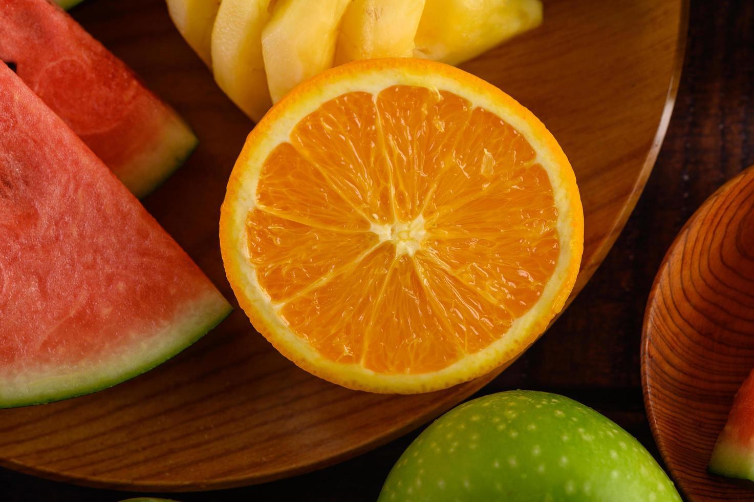 Wassermelonen, Orangen und Ananas schneiden foto