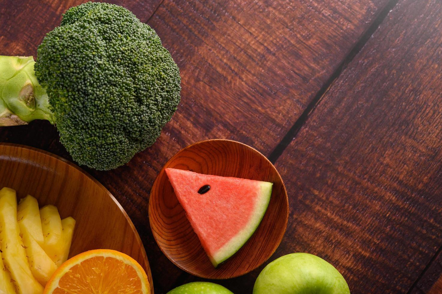 Wassermelonen, Orangen und Ananas mit Äpfeln und Brokkoli schneiden foto