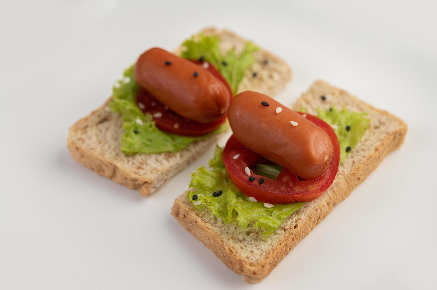 Wurst mit Tomaten und Salat auf Brot foto