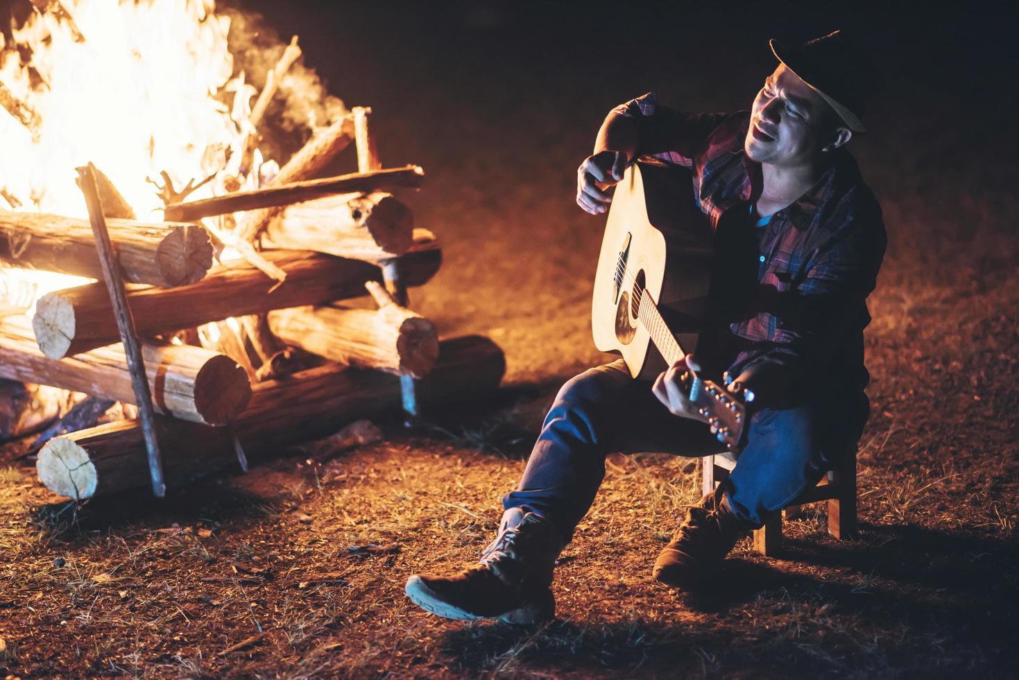 junger Mann, der am Lagerfeuer sitzt und Gitarre spielt foto