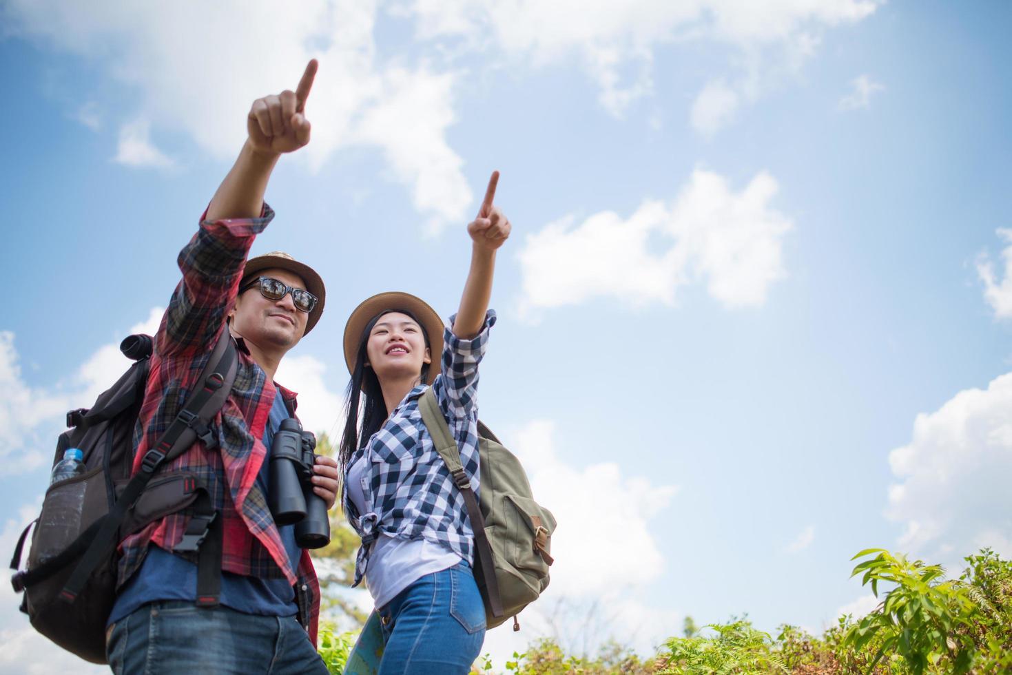 junges Paar, das mit Rucksäcken im Wald geht foto