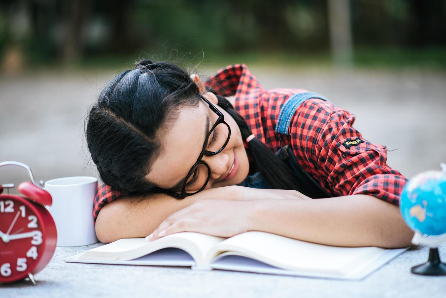 junges Mädchen, das auf Schreibtisch liegt, nachdem es draußen ein Buch gelesen hat foto