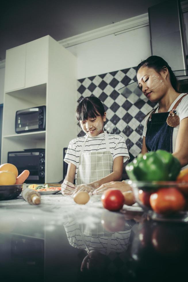 süßes kleines Mädchen und Mutter in Schürzen, die Teig in der Hauptküche abflachen foto