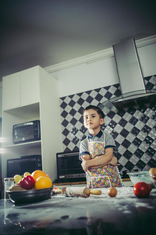 süßer kleiner Junge, der lernt, wie man stehend in der Küche kocht foto