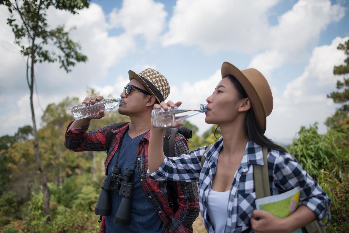 junge Wanderer trinken Wasser im Wald foto
