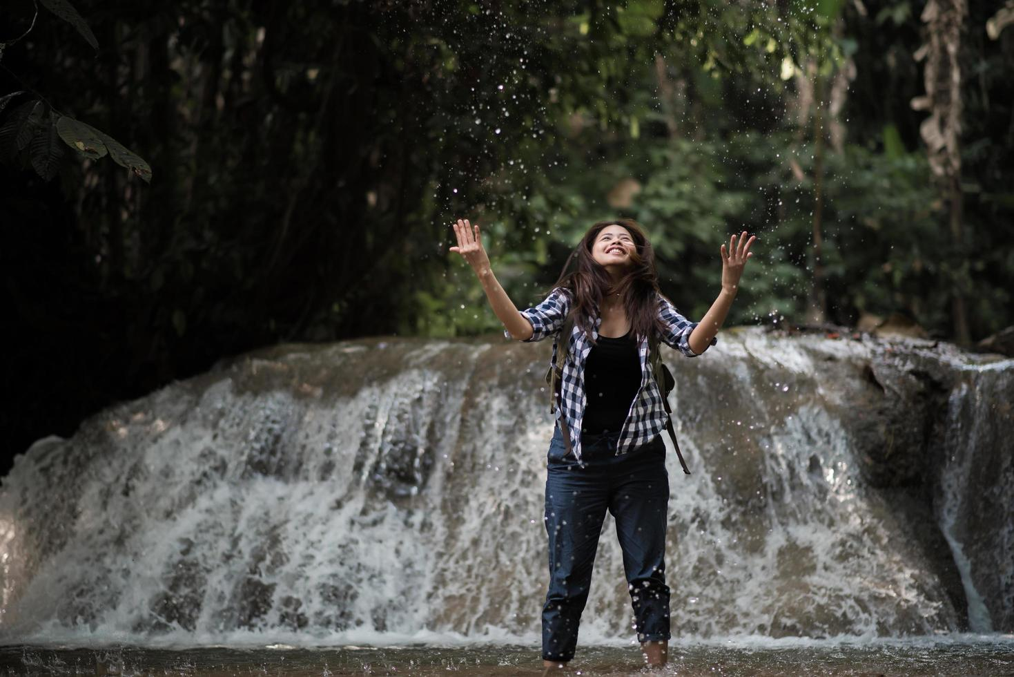 junge Frau, die Spaß unter einem Wasserfall im Wald hat foto