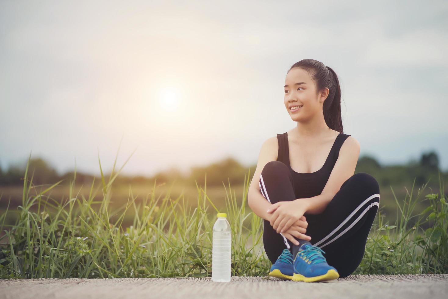 Teen Fitness-Läufer entspannen mit Wasser nach dem Training foto