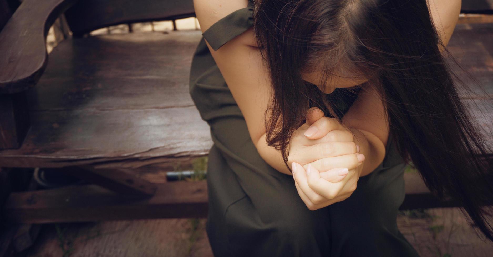 Frau, die auf der Bank betet foto