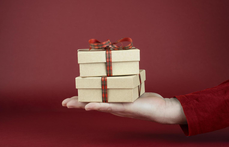 Hand des Mannes, die Geschenkboxen zum Valentinstag vor einem roten Hintergrund hält foto