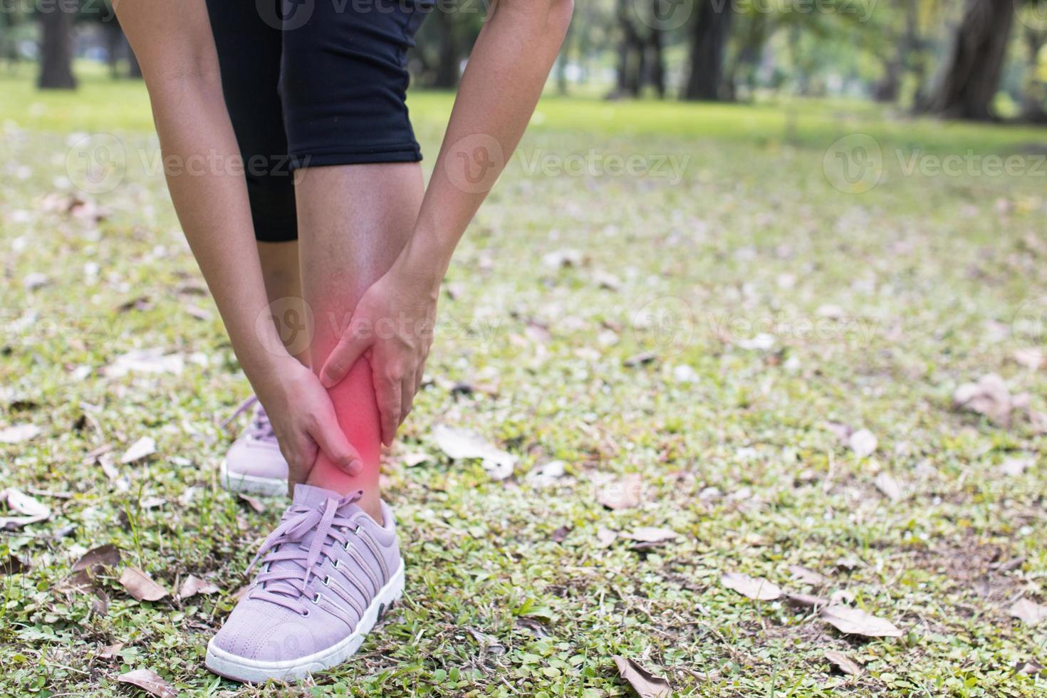 Frau hält ihren Knöchel vor Schmerzen foto