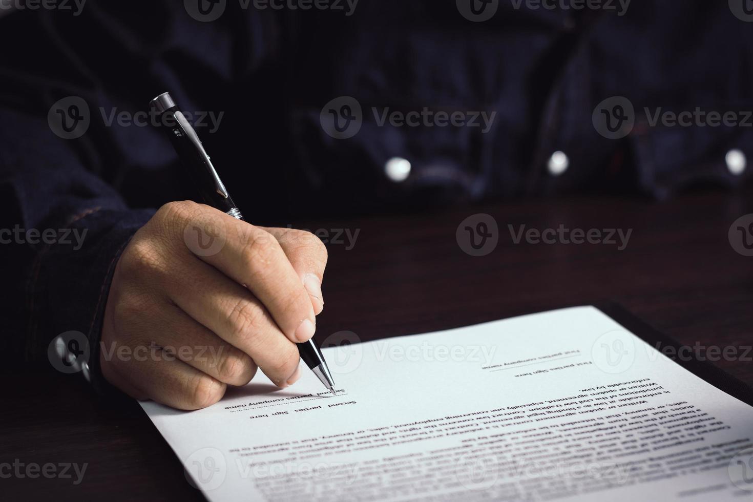 Person, die einen Vertrag unterzeichnet foto