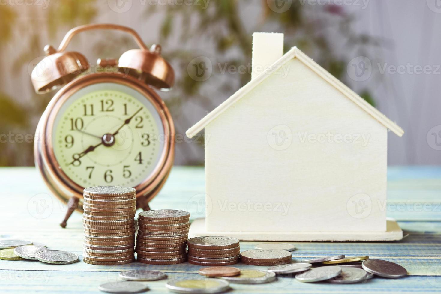 Stapel Münzen mit einem Holzhaus foto