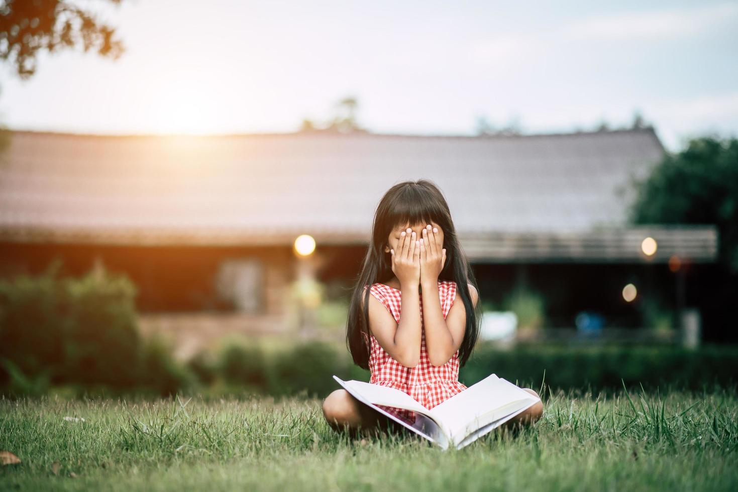 junges Mädchen, das im Garten außerhalb ihres Hauses liest foto