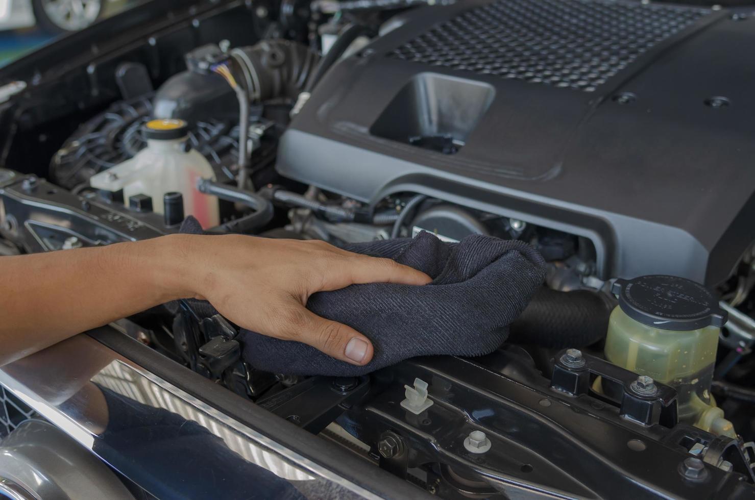 Der Mechaniker überprüft und reinigt den Motor des Autos foto