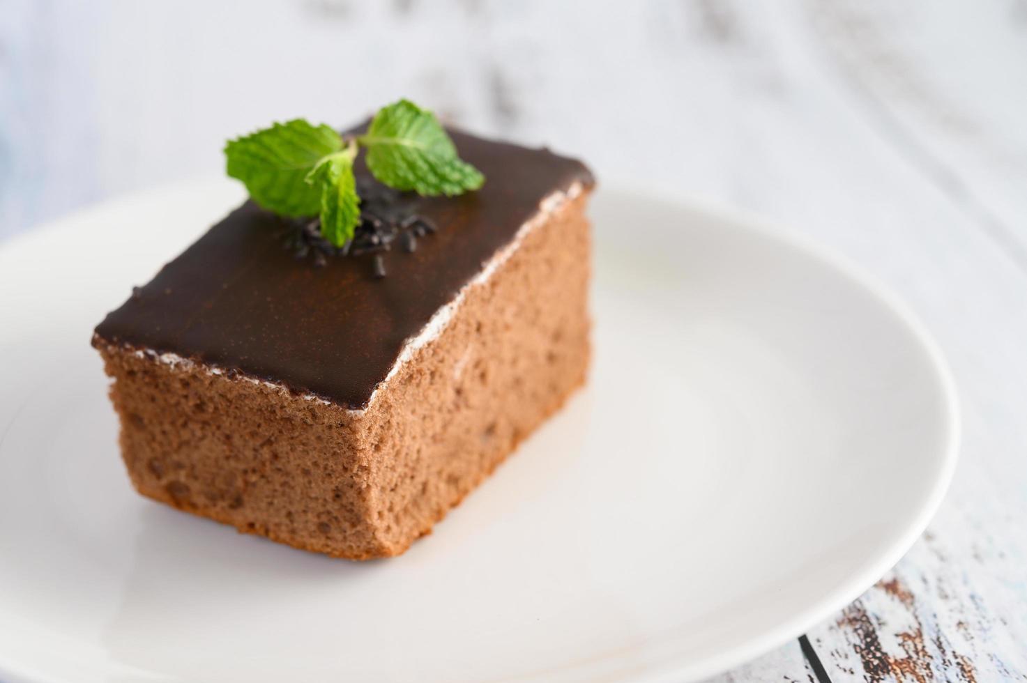 Schokoladenkuchen auf einem weißen Teller und einem weißen Holztisch foto