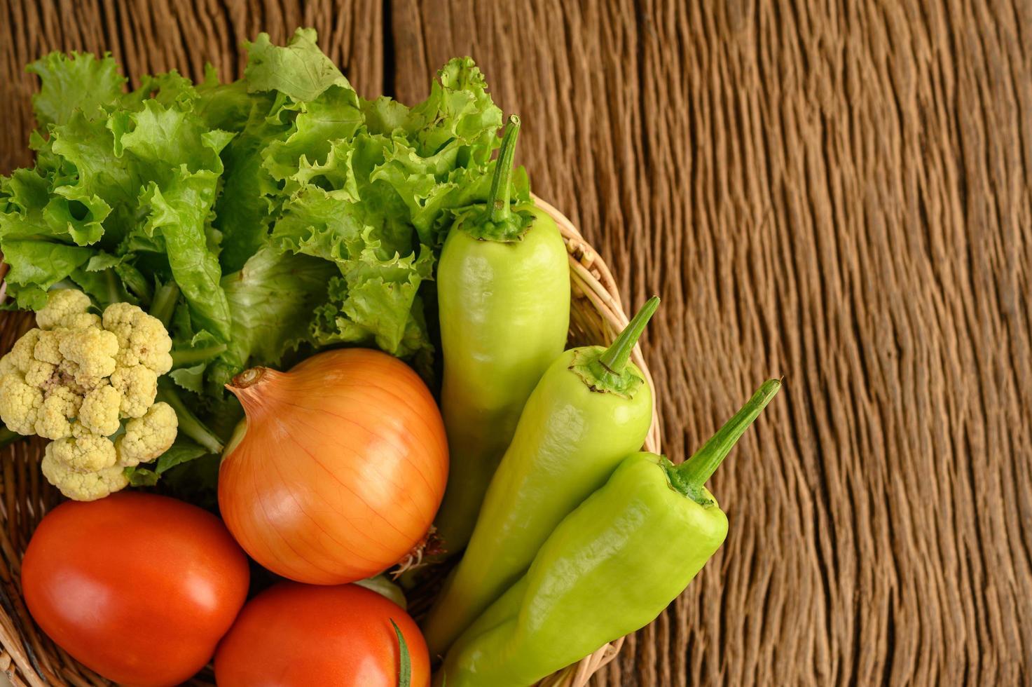 Paprika, Tomate, Zwiebel, Salat und Blumenkohl auf einem Holzkorb auf einem Holztisch foto