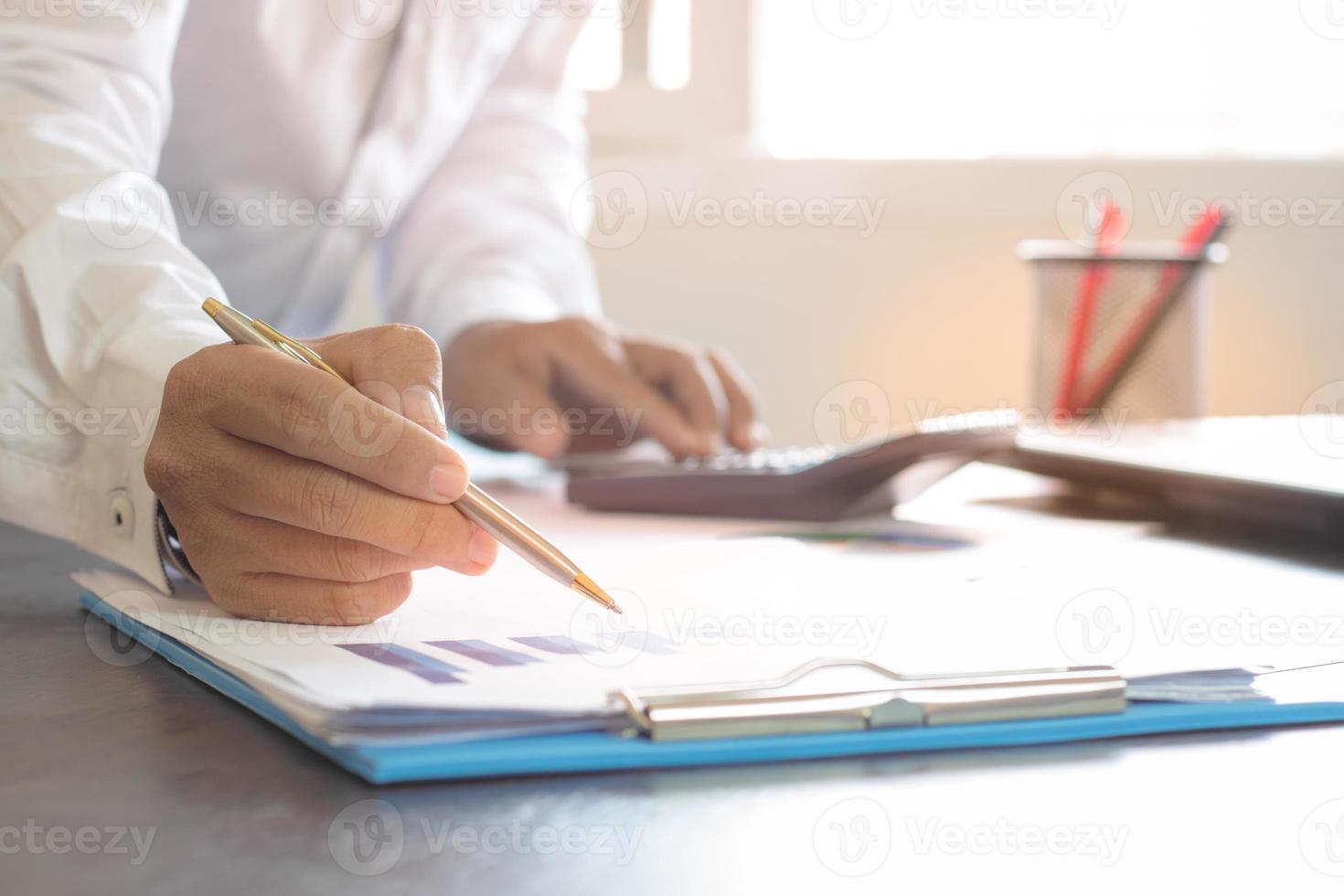 Geschäftsmann, der mit einem goldenen Stift schreibt foto