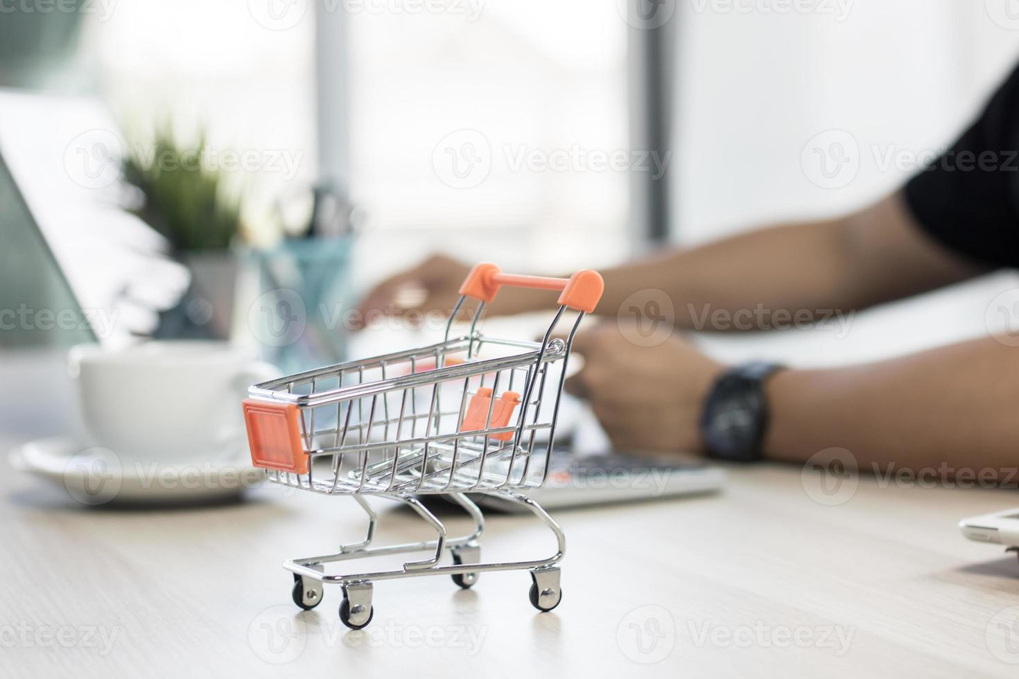 winziger Einkaufswagen auf einem Schreibtisch foto