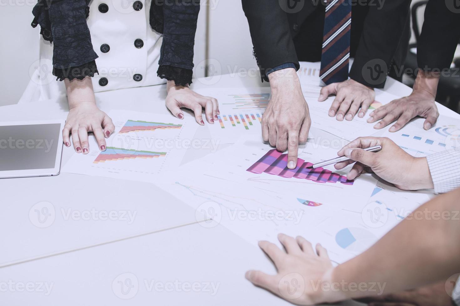 Eine Gruppe von Geschäftsleuten versammelte sich um ein Diagramm foto
