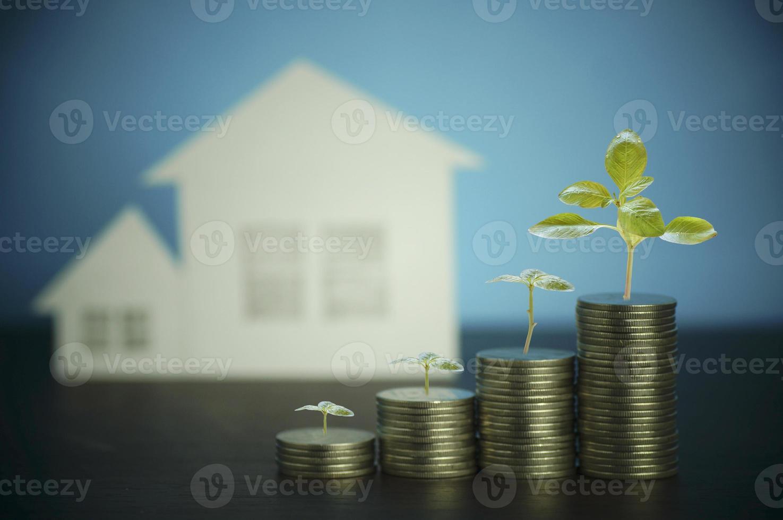 Stapel Münzen mit einem Haus im Hintergrund foto