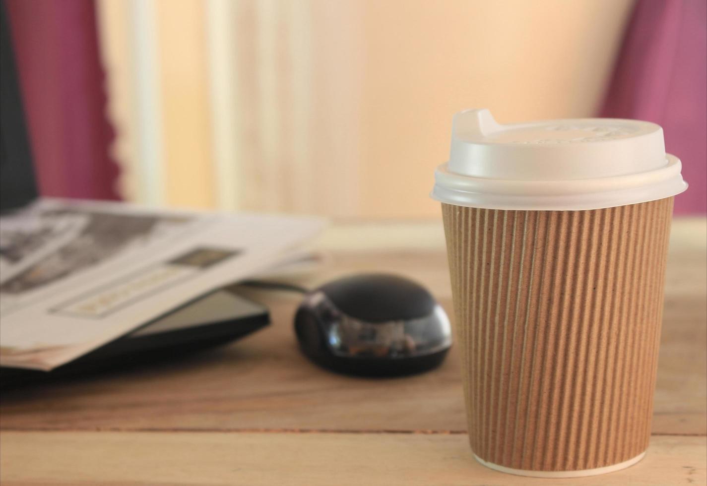 To-Go-Tasse auf Holzschreibtisch foto