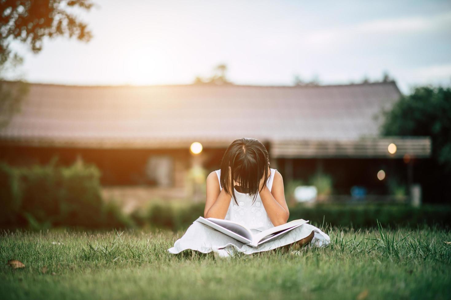 gelangweiltes Mädchen, das im Hausgarten liest foto