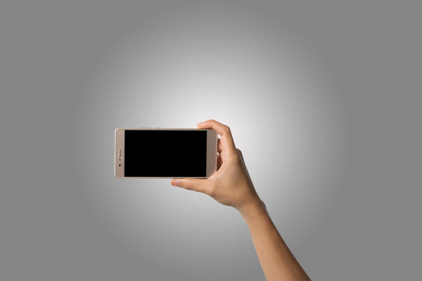 Nahaufnahme der Hand einer Frau, die ein Telefon lokalisiert auf weißem Hintergrund hält foto