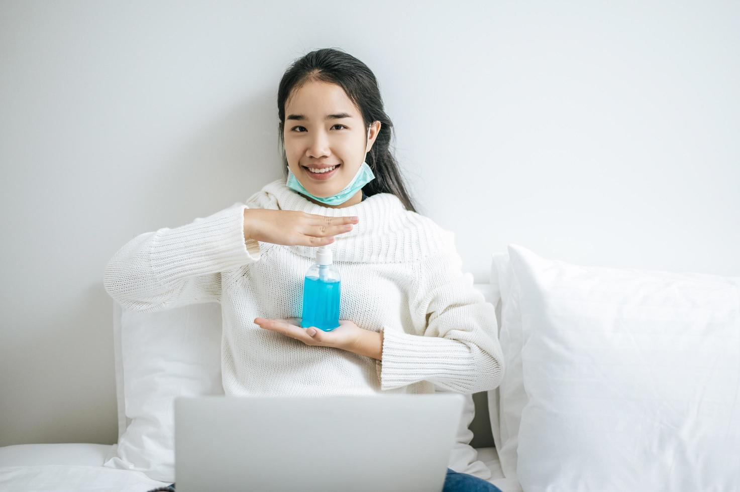 junge Frau auf Bett, die Handwaschgel hält foto