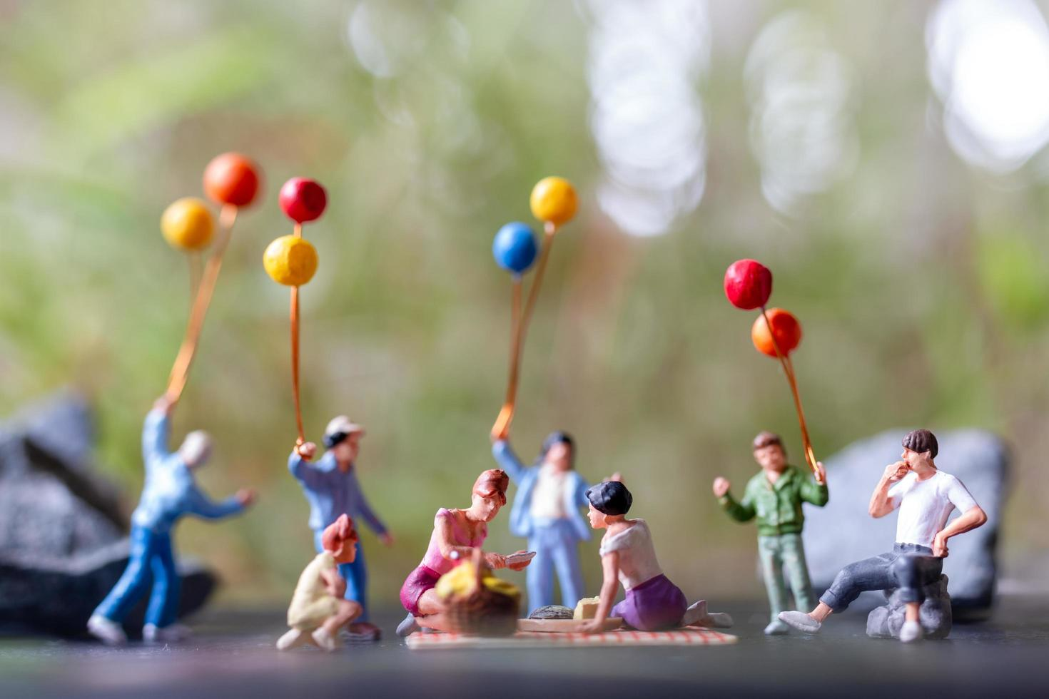 Gruppe von Miniaturmenschen, die ein Picknick machen foto