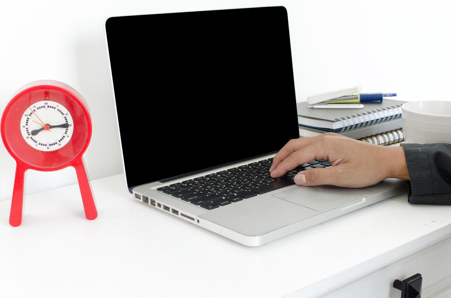 Laptop mit Uhr auf dem Schreibtisch foto