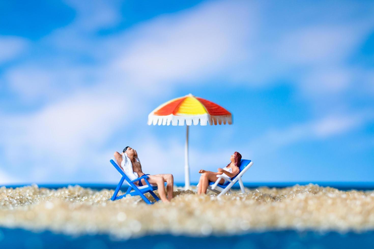 Miniaturfiguren sitzen am Strand foto