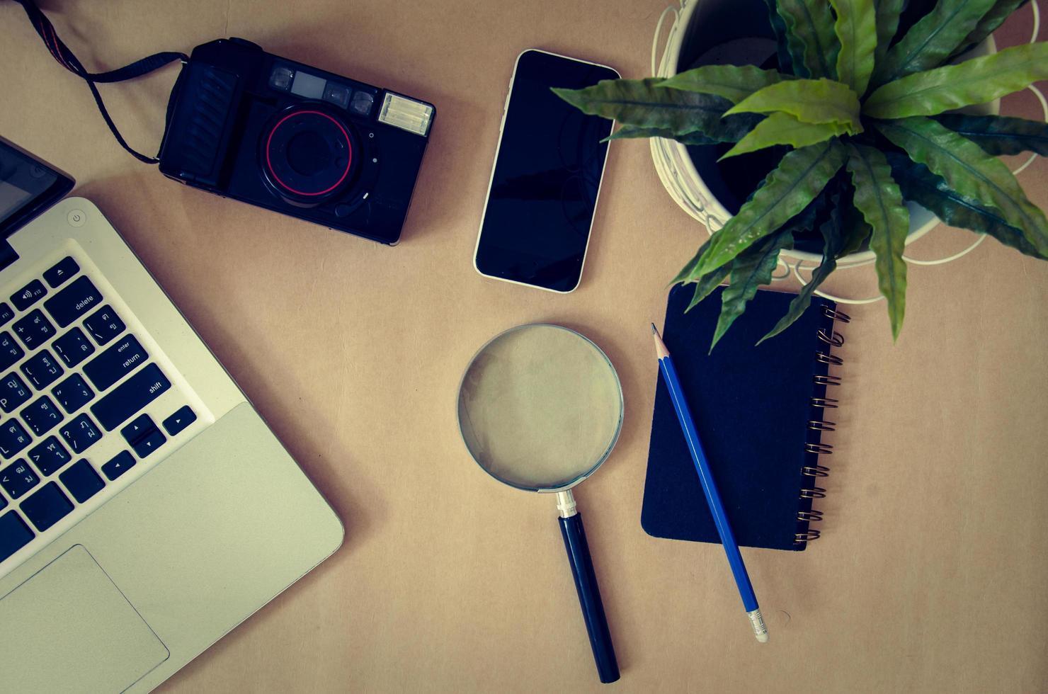 Lupe, Kamera und Telefon auf einem Schreibtisch foto