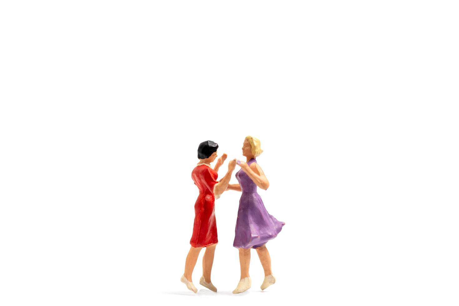 Miniaturfiguren eines lesbischen Paares, das auf weißem Hintergrund tanzt foto