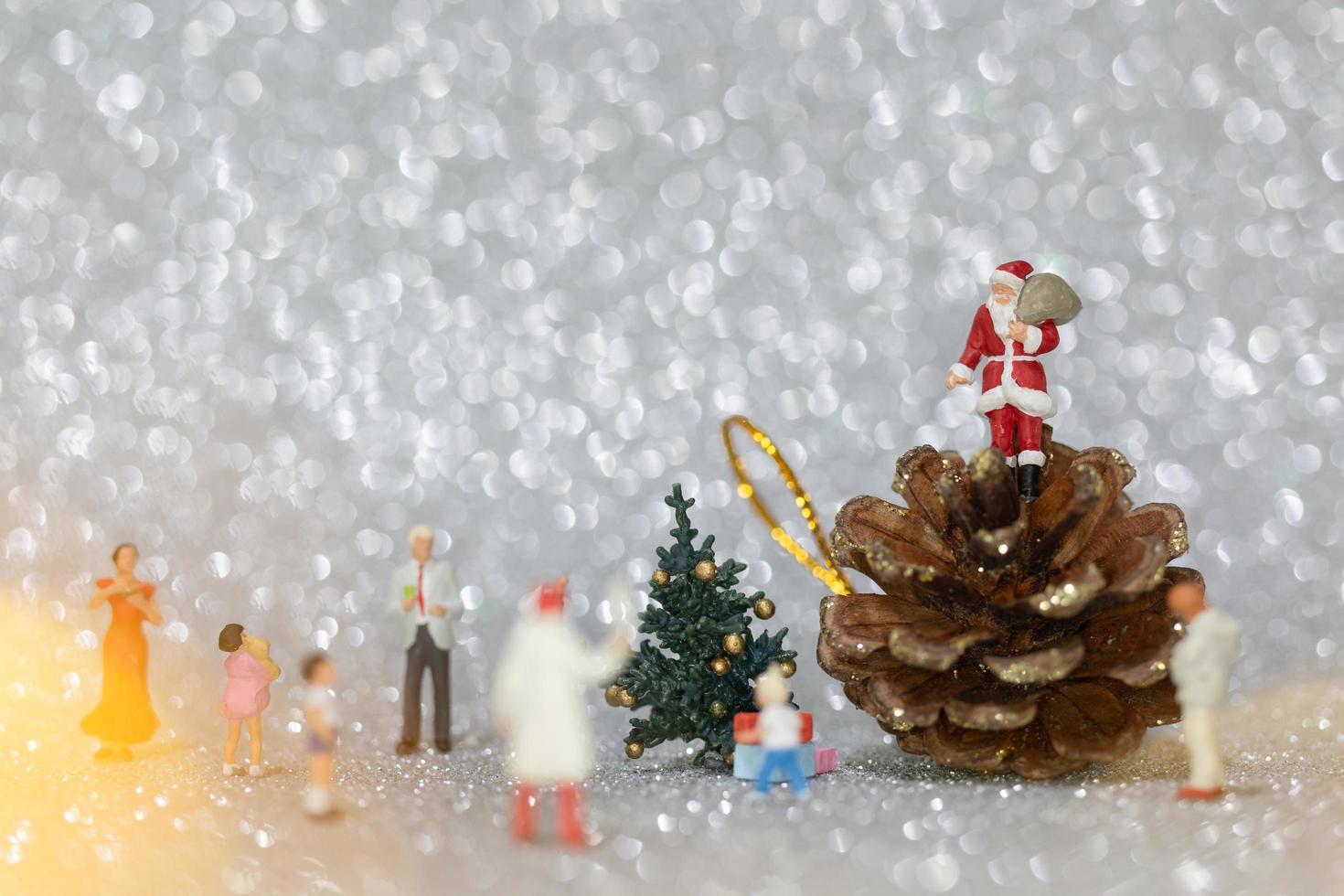 Miniaturfiguren von Menschen, die Weihnachtsschmuck aufstellen foto