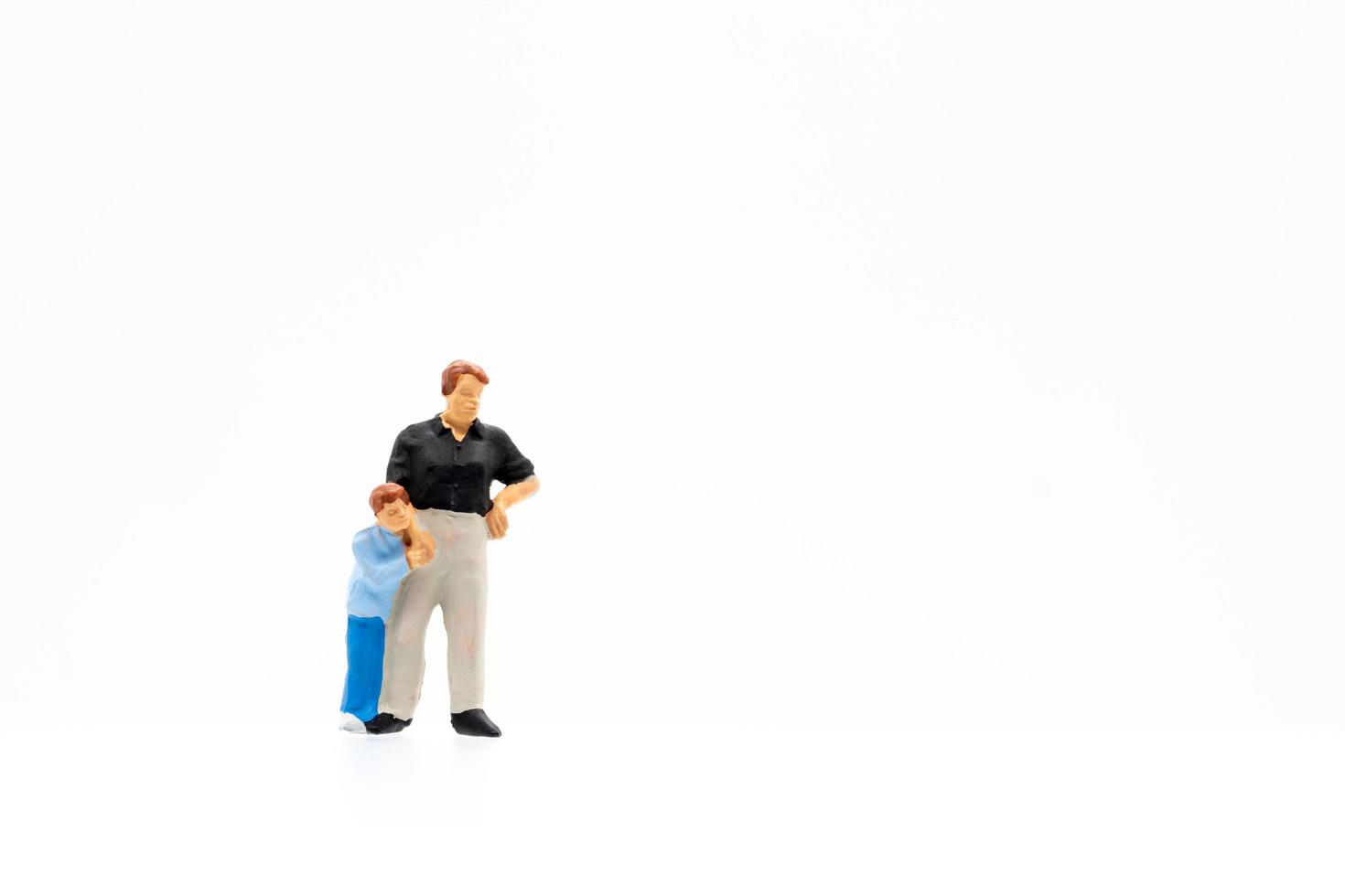 Miniaturfigur von Mutter und Sohn, die auf weißem Hintergrund stehen foto